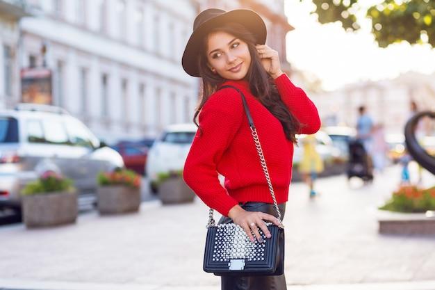 Mulher morena sedutora em roupa casual outono, andando na cidade ensolarada. pulôver de malha vermelho, chapéu preto moderno, saia de couro.