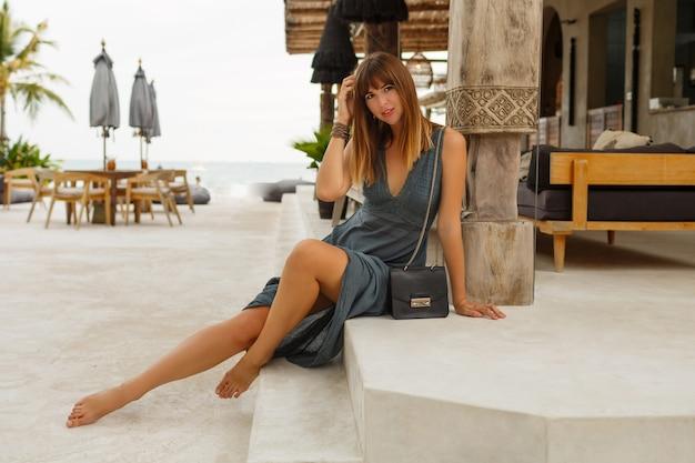 Mulher morena sedutora em um vestido sexy, posando em um elegante restaurante de praia em estilo asiático.