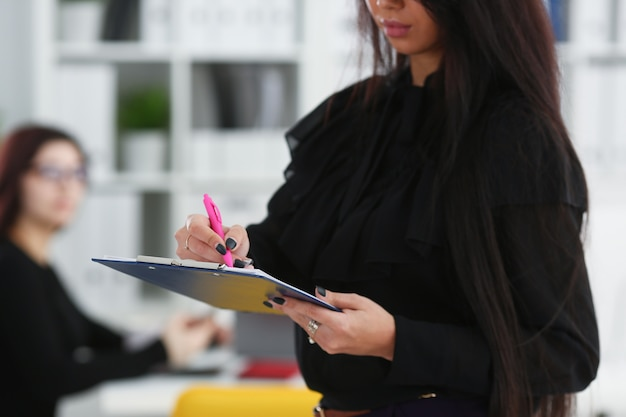 Mulher morena segurando nos braços uma caneta rosa e um papel preso com um clipe para os colegas
