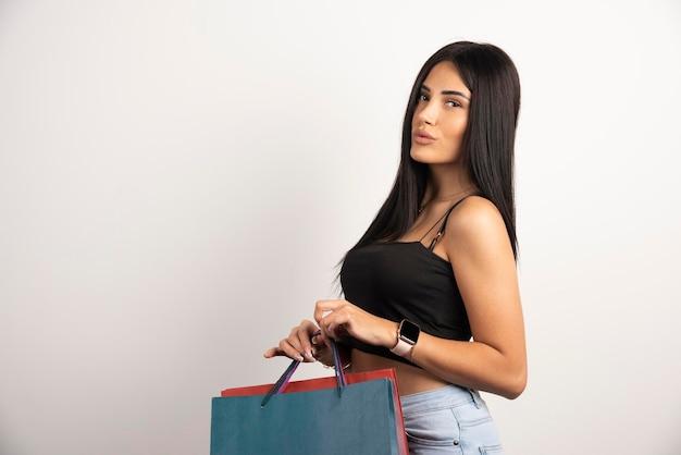 Mulher morena segurando sacolas de compras em fundo bege. foto de alta qualidade