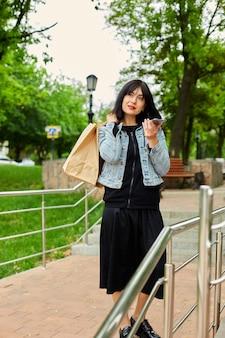 Mulher morena segurando sacolas de papel e falando ao telefone