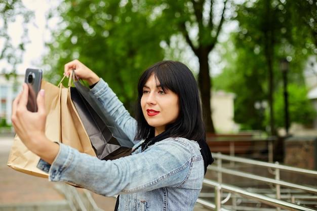 Mulher morena segurando sacolas de papel e tirando selfie pelo smartphone no parque