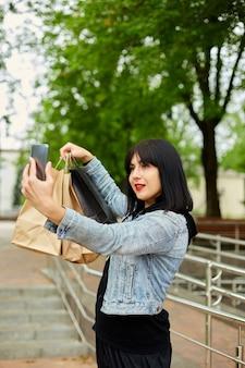 Mulher morena segurando sacolas de papel e tomando selfie por smartphone no parque, garota depois das compras.