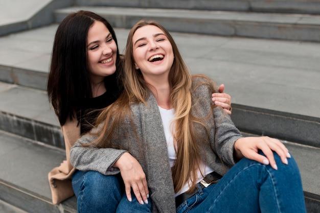 Mulher morena segurando seu amigo sorridente