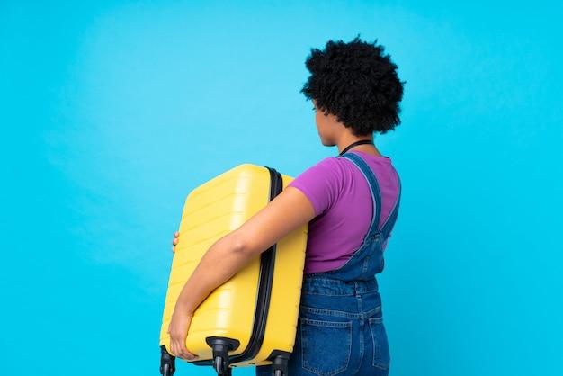 Mulher morena segurando uma mala sobre fundo azul isolado