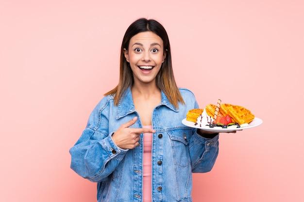 Mulher morena segurando waffles sobre parede rosa com expressão facial de surpresa