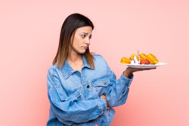 Mulher morena segurando waffles sobre parede rosa com expressão triste