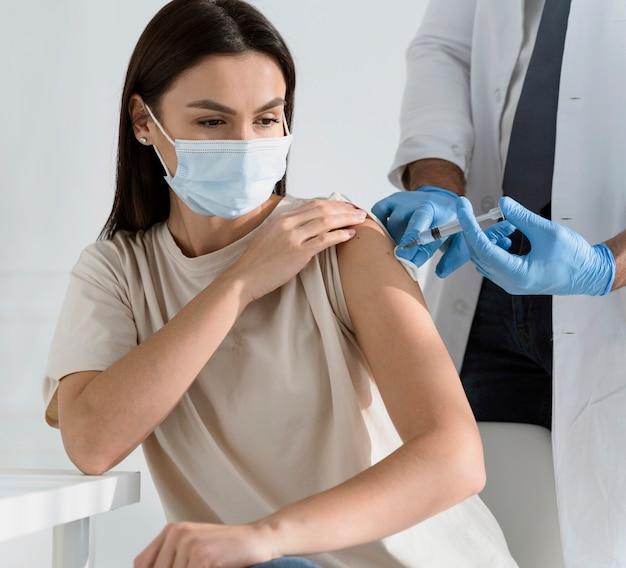 Mulher morena sendo vacinada pelo médico