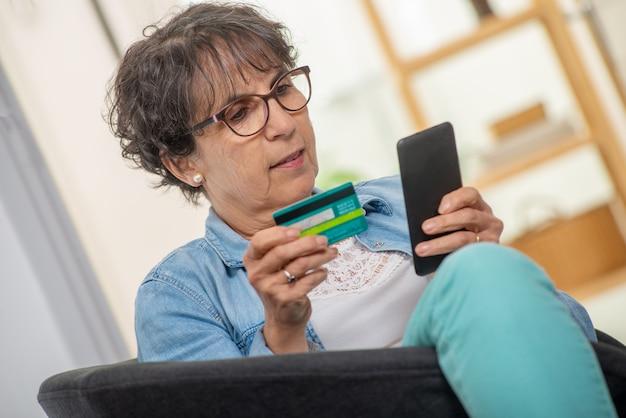 Mulher morena sênior, compras com smartphone e internet