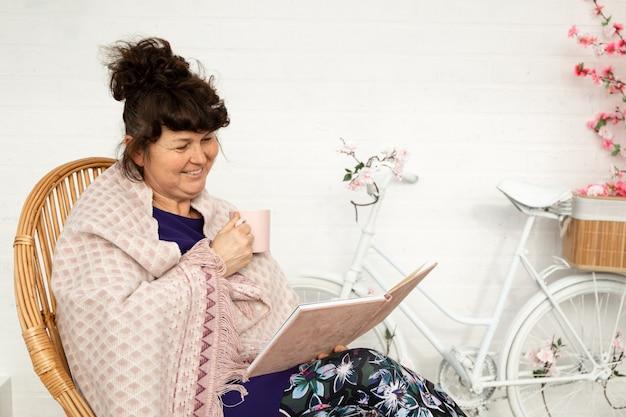 Mulher morena sênior lendo livro sentado do lado de fora na cadeira no jardim e beber café. mulher madura lendo romance no jardim de seu quintal. Foto Premium