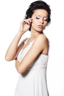Mulher morena sexy linda noiva feliz vestido de noiva branco com penteado e maquiagem brilhante