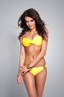 Mulher morena sexy posando de biquíni amarelo