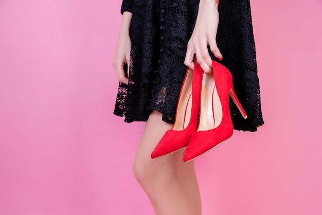 Mulher morena sexy vestido preto segurando sapatos vermelhos em fundo rosa