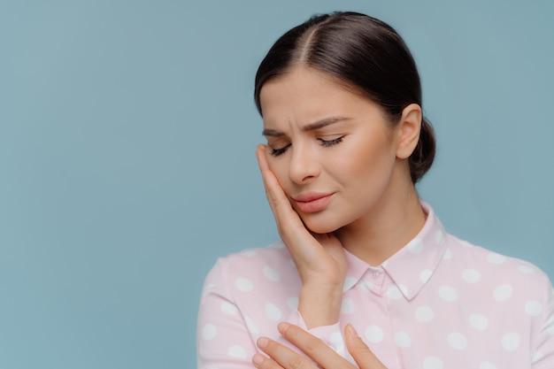 Mulher morena sofre de dor terrível de dentes fortes