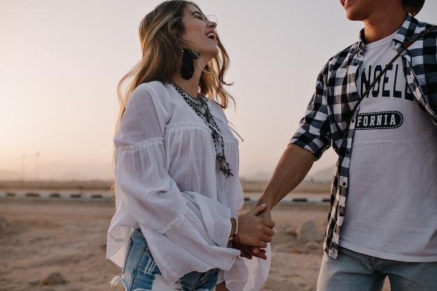 Mulher morena sonhadora em blusa vintage branca anda com o namorado de camisa quadriculada e rindo. retrato de uma jovem sorridente e bonita se divertindo em um encontro ao ar livre com um céu incrível