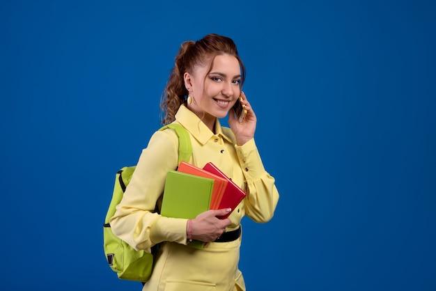 Mulher morena sorridente adulta fazendo anotações na agenda e falando no celular