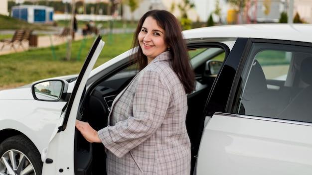 Mulher morena sorridente ao lado de um carro branco