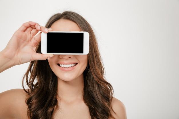 Mulher morena sorridente, cobrindo os olhos e mostrando a tela do smartphone em branco sobre cinza