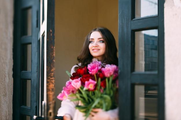 Mulher morena sorridente com buquê de tulipas saindo de casa.