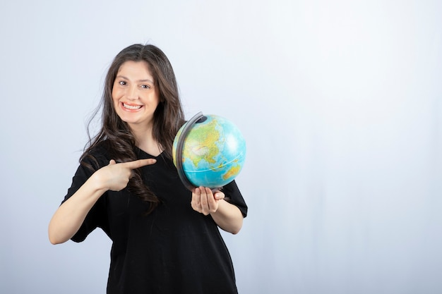 Mulher morena sorridente com cabelo comprido apontando para o globo do mundo e posando