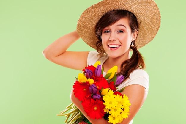 Mulher morena sorridente com chapéu e flor de primavera