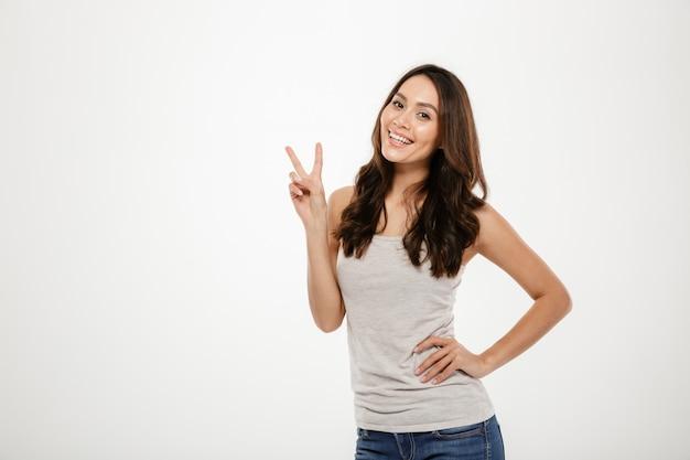 Mulher morena sorridente com o braço no quadril, mostrando o gesto de paz e olhando para a câmera sobre cinza