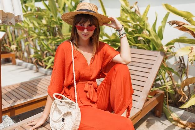 Mulher morena sorridente com roupa laranja elegante e chapéu de palha, relaxando na espreguiçadeira perto da piscina.