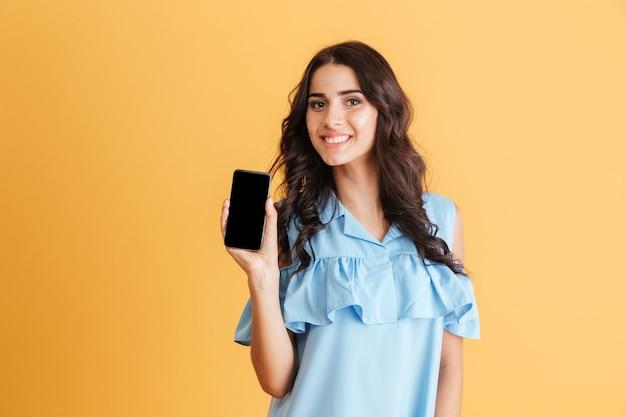 Mulher morena sorridente com vestido azul mostrando a tela do smartphone em branco isolada