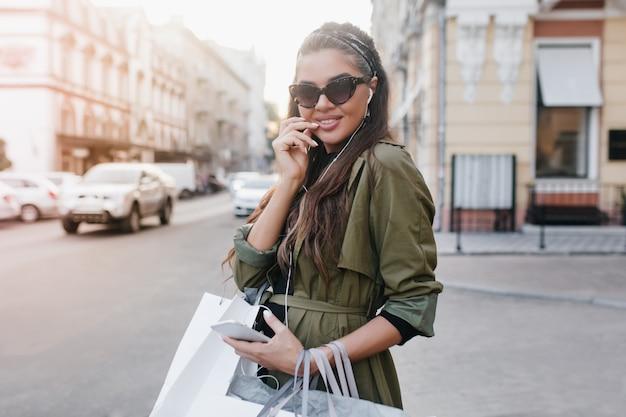 Mulher morena sorridente de óculos escuros andando pela cidade e ouvindo música