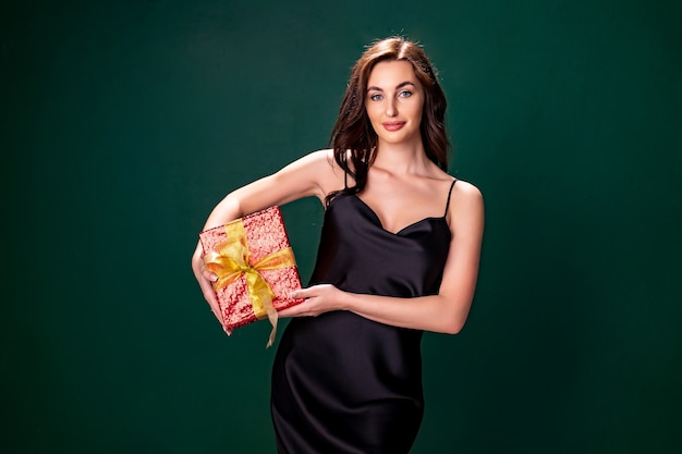 Mulher morena sorridente de vestido preto levanta a caixa de presente vermelha com o conceito de férias de arco dourado