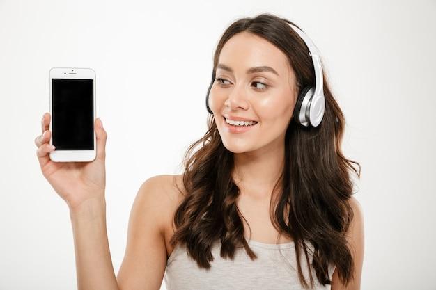 Mulher morena sorridente em fones de ouvido, mostrando a tela do smartphone em branco e olhando para ele sobre cinza
