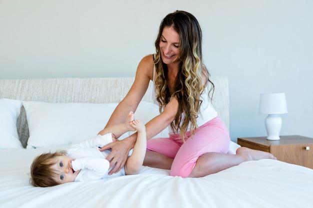 Mulher morena sorridente está segurando um bebê fofo enquanto está sentado na cama