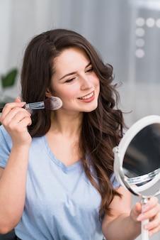Mulher morena sorridente fazendo maquiagem e olhando para o espelho