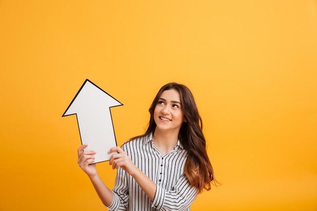 Mulher morena sorridente na camisa apontando com seta de papel acima