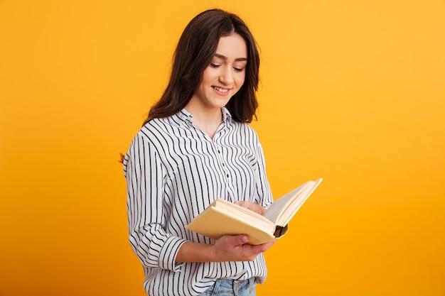 Mulher morena sorridente na camisa lendo livro