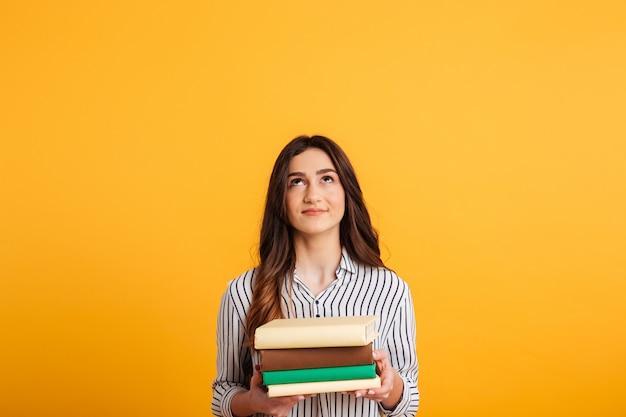 Mulher morena sorridente na camisa segurando livros e olhando para cima
