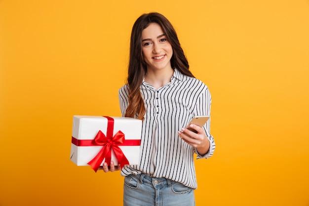 Mulher morena sorridente na camisa, segurando o smartphone e a caixa de presente