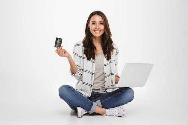 Mulher morena sorridente na camisa, sentada no chão com o computador portátil e cartão de crédito enquanto olha para a câmera sobre cinza