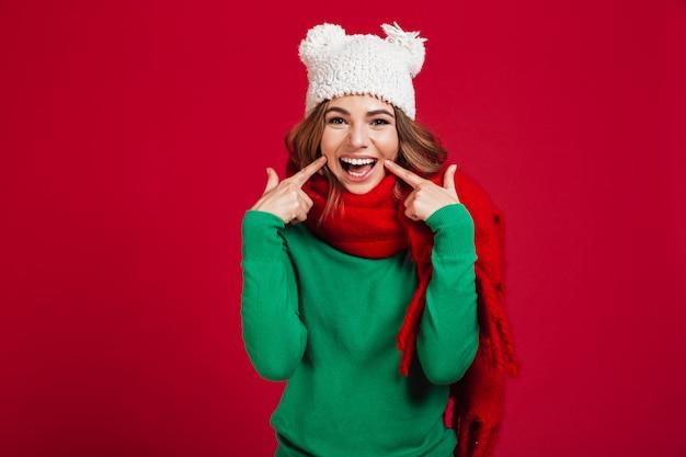Mulher morena sorridente na camisola, chapéu engraçado e cachecol