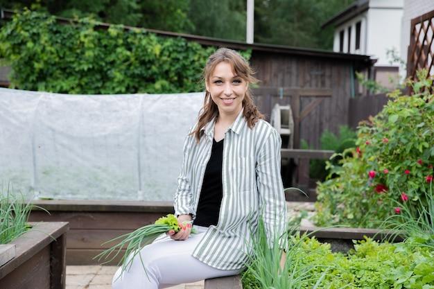 Mulher morena sorridente posando com cebolas e alface nas mãos no jardim