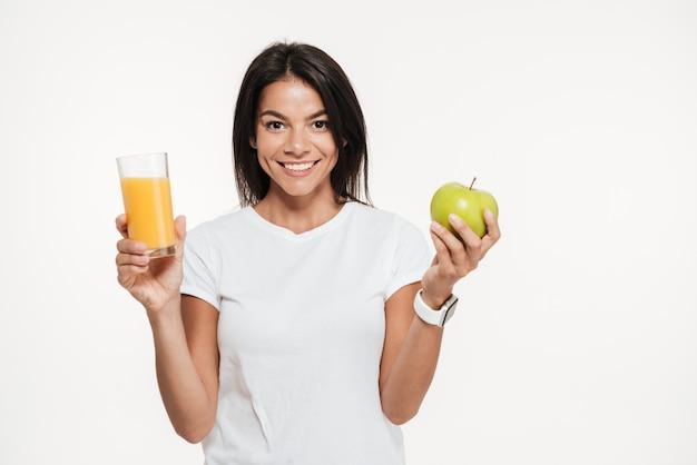 Mulher morena sorridente segurando o copo de suco de laranja