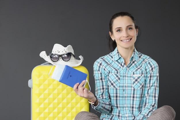 Mulher morena sorridente segurando o passaporte com passagem e máscara ao lado da mala de viagem turística