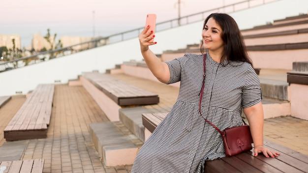 Mulher morena sorridente tirando uma selfie