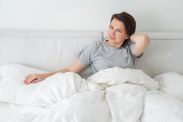 Mulher morena sorridente, vestindo pijama, sentado na cama no quarto