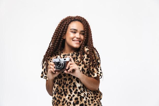 Mulher morena sorrindo e fotografando na câmera retro em pé, isolado contra uma parede branca