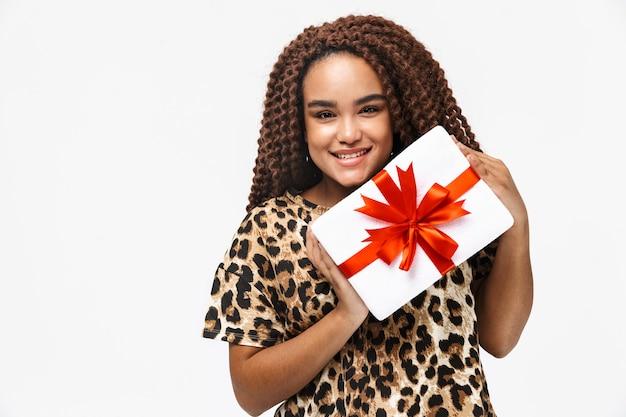 Mulher morena sorrindo e segurando uma caixa de presente com um laço em pé, isolada contra uma parede branca
