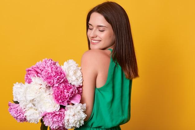 Mulher morena suave com vestido verde, segurando flores de peônia nas mãos