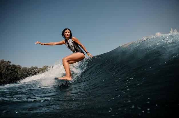Mulher morena surfando em uma prancha de surf no mar