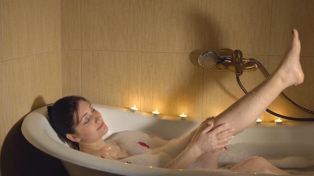 Mulher morena tomando banho com espuma e pétalas de rosa.