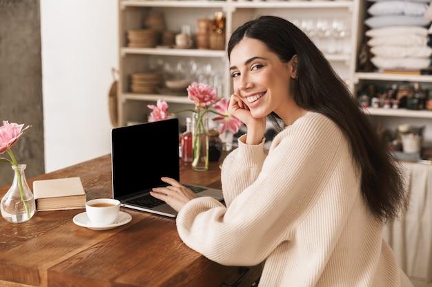 Mulher morena tomando café e usando laptop na cozinha de casa